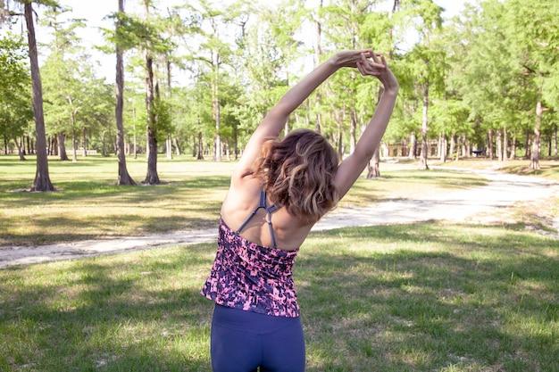 Donna bionda in un parco che fa yoga e stretching.