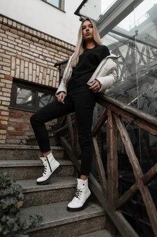 Donna bionda in una giacca bianca in jeans alla moda neri si riposa su una scala d'epoca in pietra