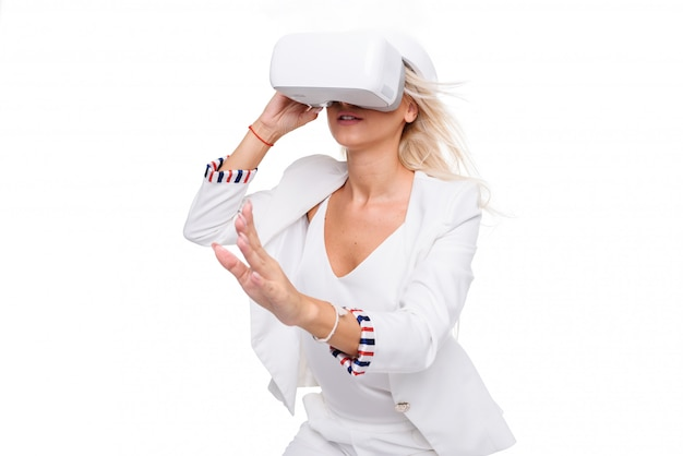 Donna bionda in suite bianca con occhiali per realtà virtuale. studio sparato su spazio bianco
