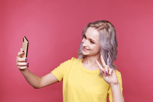 Giovane donna alla moda bionda con capelli ricci che mostra la pace e che fa foto isolata in studio