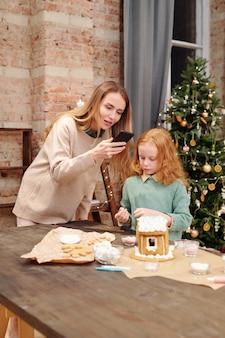 Giovane donna bionda con lo smartphone sul tavolo che cattura foto della casa di marzapane fatta in casa, mentre in piedi dalla sua piccola figlia carina