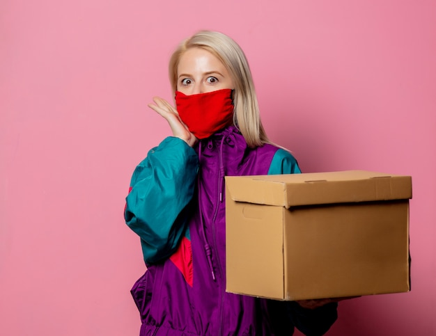 Bionda in abiti anni '80 e maschera con scatola