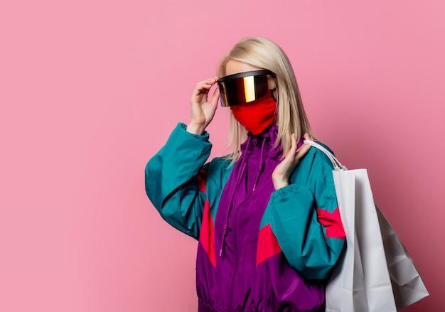Bionda in abiti anni '80 e maschera per il viso con borse della spesa