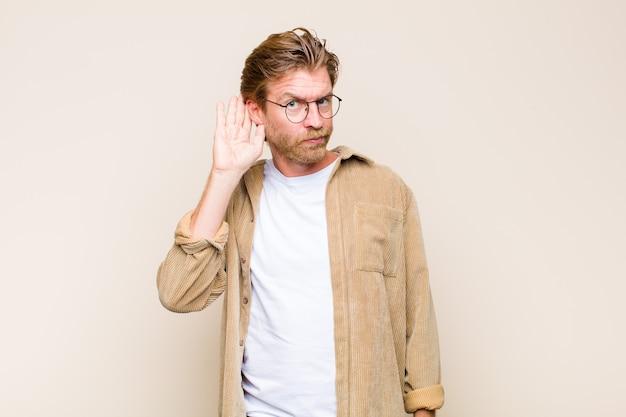 Uomo caucasico adulto biondo che sembra serio e curioso, ascolta, cerca di ascoltare una conversazione segreta o pettegolezzi, origliare