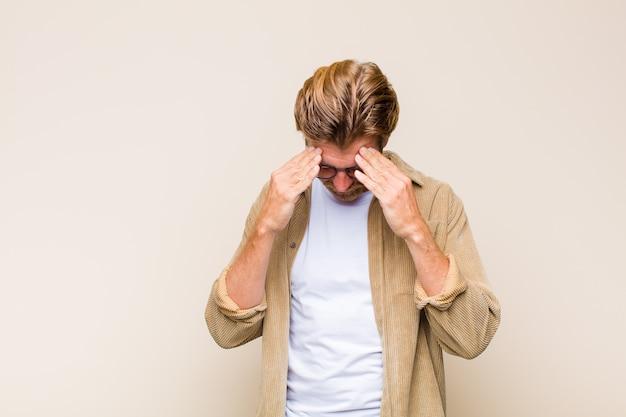 Uomo caucasico adulto biondo che sembra stressato e frustrato, lavorando sotto pressione con un mal di testa e turbato da problemi