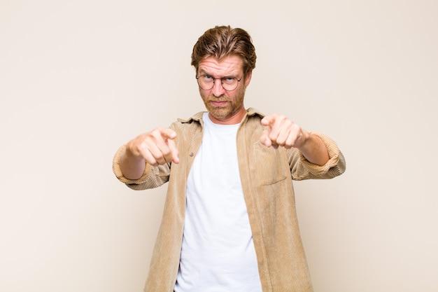 Uomo caucasico biondo adulto che indica davanti con entrambe le dita e l'espressione arrabbiata, dicendoti di fare il tuo dovere