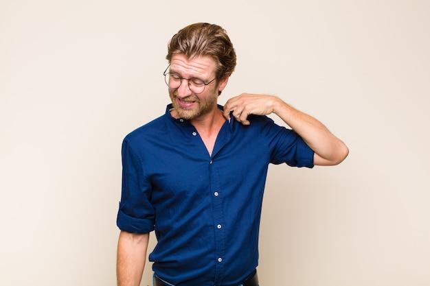 Uomo adulto biondo che si sente stressato, ansioso, stanco e frustrato, tira il collo della camicia, sembra frustrato dal problema
