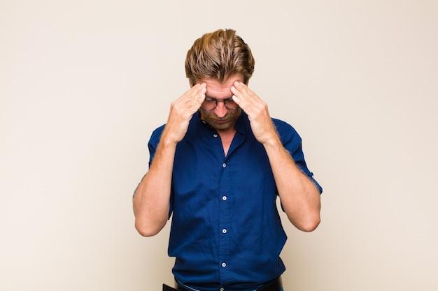 Uomo adulto biondo che sembra stressato e frustrato, lavorando sotto pressione con un mal di testa e turbato da problemi
