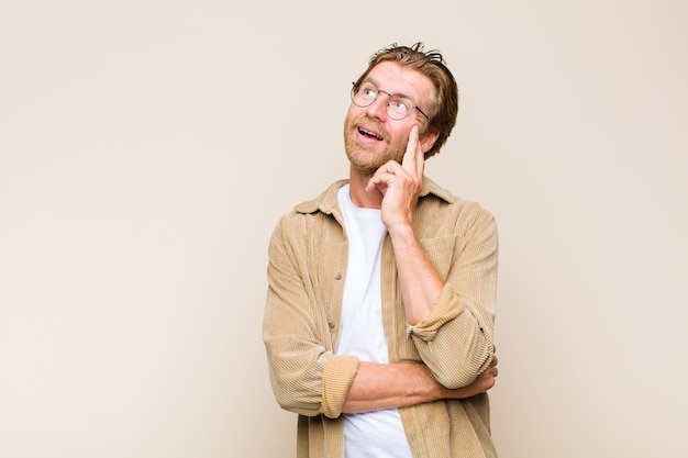 Uomo adulto biondo sorridente felicemente e fantasticando o dubitando, guardando al lato