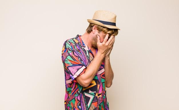 Uomo biondo adulto viaggiatore che copre gli occhi con le mani con uno sguardo triste e frustrato di disperazione, pianto, vista laterale