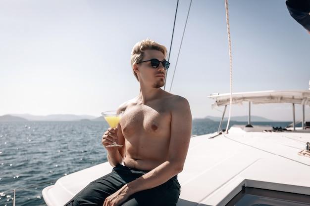 Uomo biondo e barbuto in posa, con in mano un bicchiere di bevanda fredda in mano sul suo costoso yacht bianco.
