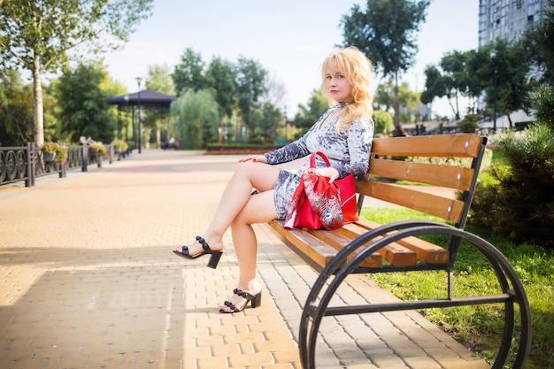 Bionda in un vestito blu in posa su una panchina in un parco cittadino