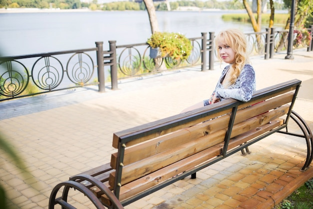 Bionda in un vestito blu in posa vicino al fiume in un parco cittadino