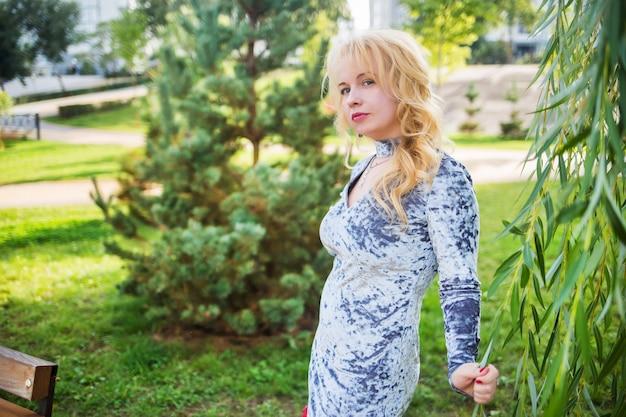 Bionda in un vestito blu in posa vicino all'albero in un parco cittadino