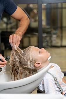 Ragazzo biondo nel negozio di barbiere lavarsi i capelli prima del taglio di capelli