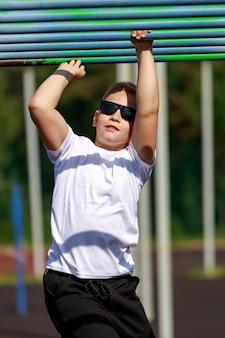 Un ragazzo biondo con gli occhiali scuri si esercita su un campo sportivo. foto di alta qualità