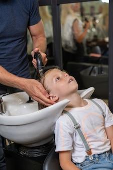 Un ragazzo biondo si fa lavare i capelli in un barbiere prima di tagliarsi i capelli
