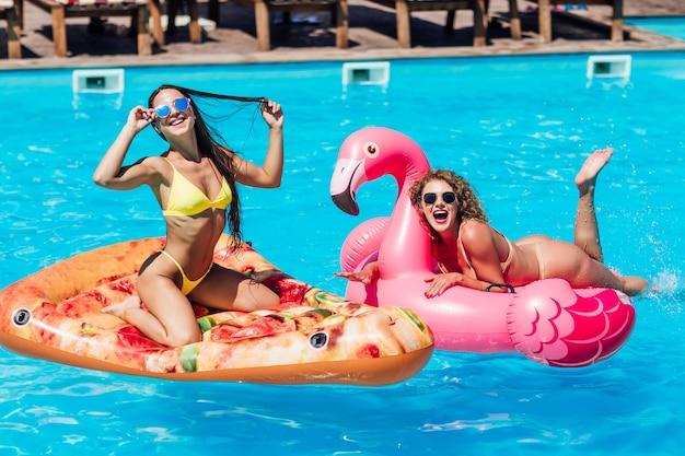 Ragazze bionde e brune che si divertono e ridono su un materasso galleggiante per piscina gonfiabile per pizza in bikini. le ragazze abbronzate attraenti si trovano al sole in vacanza.