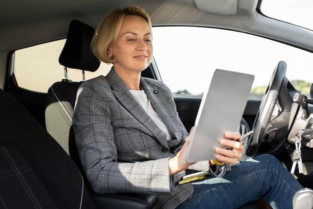 Donna d'affari bionda che guarda un tablet nella sua auto