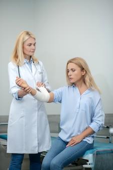 Medico premuroso bionda che applica bendaggio elastico sull'avambraccio del paziente mentre è seduto tranquillamente sul divano