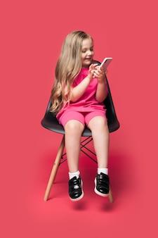 La ragazza caucasica bionda è seduta su una sedia e sorride utilizzando una parete rossa dello studio del telefono