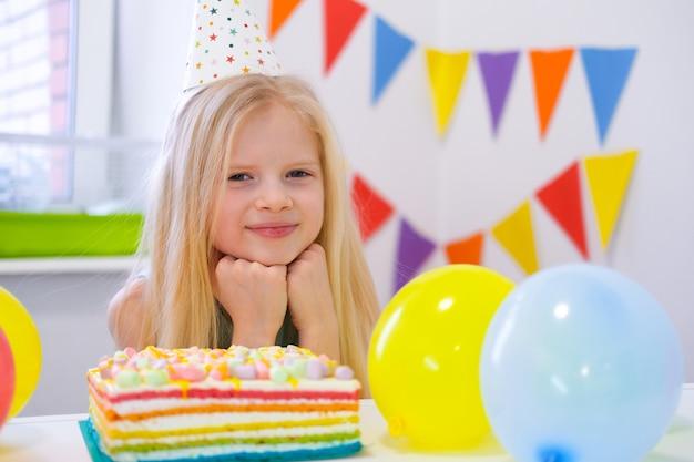 La ragazza caucasica bionda si siede pensosamente e sognante al tavolo festivo vicino alla torta arcobaleno di compleanno e fa un desiderio. guardando la fotocamera. sfondo colorato con palloncini