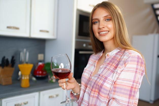 Donna felice caucasica bionda con un bicchiere di vino rosso in piedi nella sua cucina