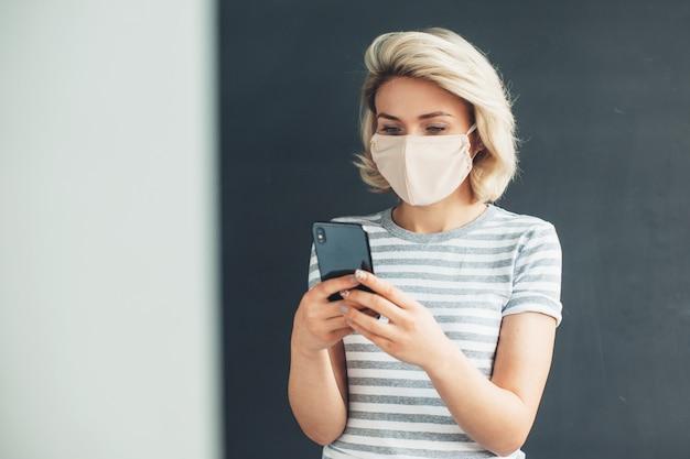 Signora bionda caucasica con maschera in chat sul cellulare a casa