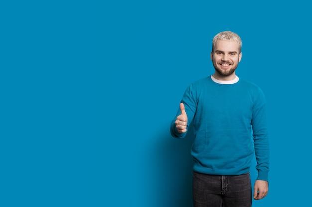 L'uomo caucasico biondo con la barba sta stringendo la mano con qualcuno mentre su una parete blu con spazio libero