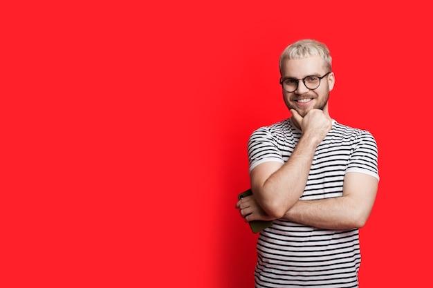 Uomo caucasico biondo con gli occhiali in posa su uno sfondo rosso con spazio libero toccando il mento e guardando la parte anteriore