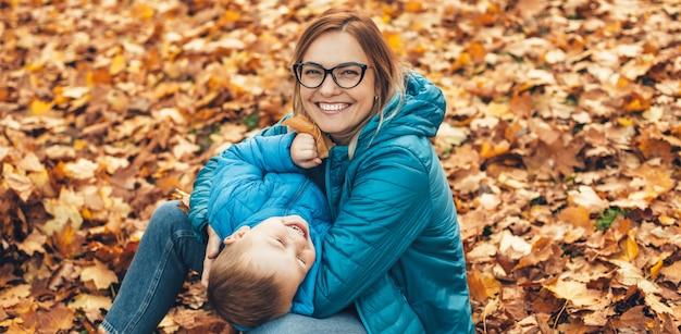 La madre caucasica bionda con gli occhiali si è vestita in vestiti blu e suo figlio che gioca a terra con le foglie