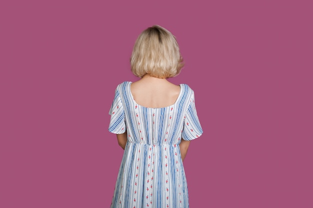 Bionda donna caucasica guardando a sfondo viola mentre indossa un abito