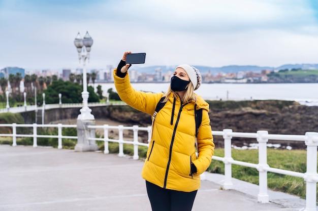 Una donna caucasica bionda con una maschera usa il telefono in una zona verde della città.