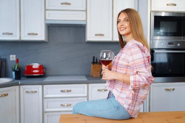 Donna caucasica bionda con un bicchiere di vino rosso in piedi nella sua cucina