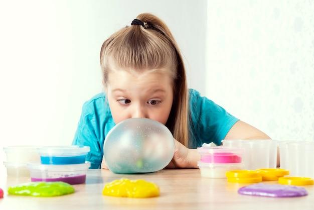 Un bambino biondo soffia una bolla di melma