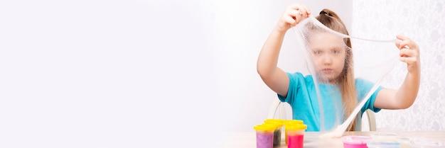 Un bambino biondo sta giocando con una melma