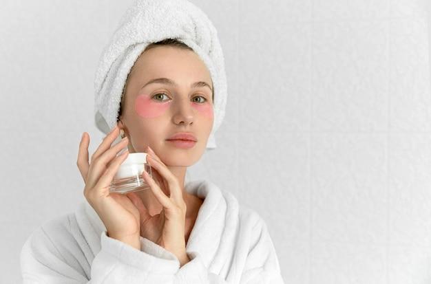 Giovane donna bionda carina con bende rosa in bagno bianco