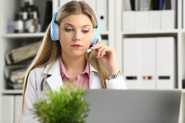 Bionda medico parlando al paziente con auricolare wireless