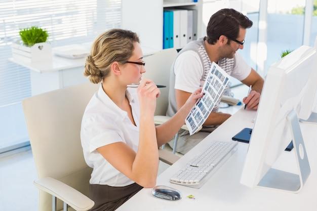 Redattore biondo che esamina il foglio di contatto al suo scrittorio