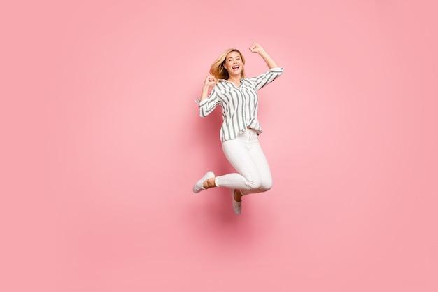 Signora bionda alla moda in posa contro il muro rosa