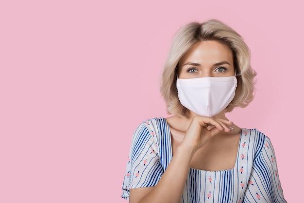 La donna bionda alla moda indossa una maschera medica sul viso e toccandosi il mento sta pubblicizzando qualcosa sul muro rosa con spazio libero