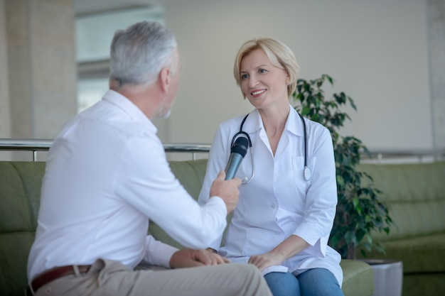 Dottoressa bionda seduta sul divano, parlando nel microfono, rispondendo alle domande del giornalista maschio dai capelli grigi