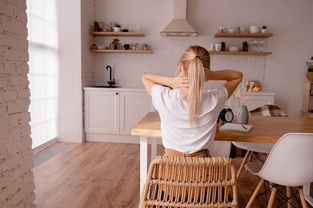 Femmina bionda seduta al tavolo e massaggiandosi il collo.