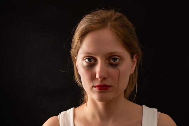 Femmina bionda con espressione triste dalla parte anteriore su sfondo nero.