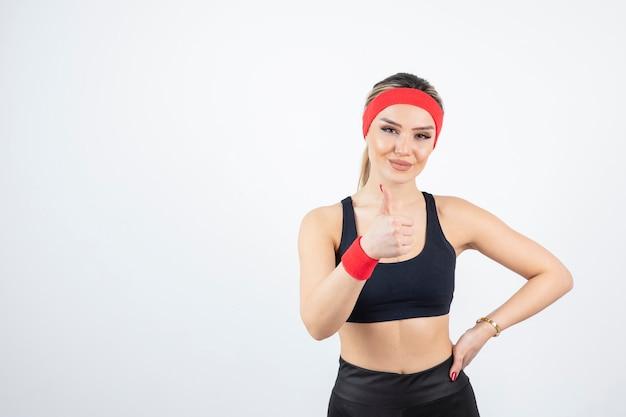 Donna bionda adatta in abiti sportivi neri in piedi e mostrando pollice in su.
