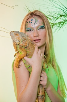 Una bionda in modo gentile con un predatore selvaggio tra le mani. iguana in cattività