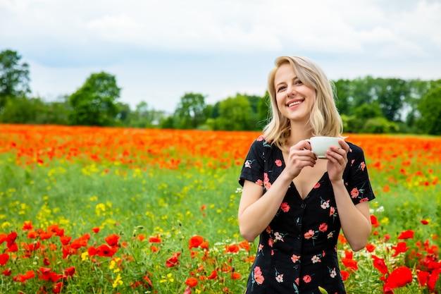 La ragazza bionda in bello vestito con la tazza di caffè nel campo dei papaveri sistema nell'ora legale