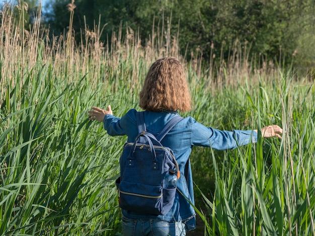 Ragazza bionda in un vestito di jeans, camminando lungo un sentiero nell'erba alta