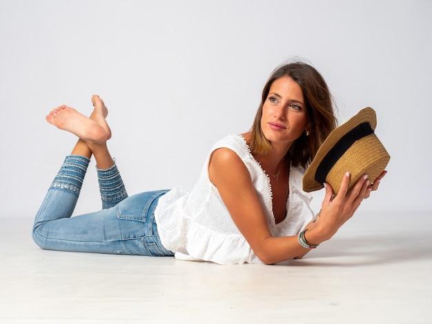 Ragazza bionda vestita in jeans, camicia bianca e un cappello sdraiato sul pavimento