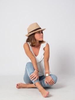 Ragazza bionda vestita in jeans, camicia bianca e un cappello seduto sul pavimento
